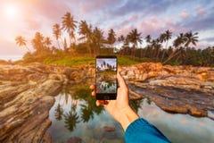 Mit Smartphone in der Hand fotografieren kleines Auto auf Dublin-Stadtkarte Sonnenuntergang auf einem tropischen Strand Stockfoto