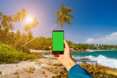 Mit Smartphone in der Hand fotografieren kleines Auto auf Dublin-Stadtkarte Sonnenuntergang auf einem tropischen Strand Lizenzfreie Stockfotos
