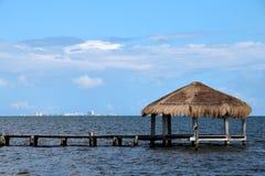 Mit Stroh gedeckter Cabana auf Dock mit Cancun auf dem Horizont stockbild