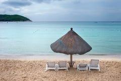Mit Stroh gedeckter Regenschirm mit Strandstühlen Lizenzfreie Stockfotos
