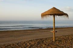 Mit Stroh gedeckter Sonnenschutz in einem Strand Stockbild