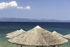 Mit Stroh gedeckter Strandschirm in Griechenland-Erholungsort Lizenzfreie Stockfotografie