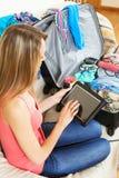 Mit Tablette zu besuchende Mädchengrasenplätze vor Urlaub Stockbild