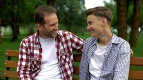 Mit Vater auf Bank sprechender, Geheimnissen sagender und lächelnder jugendlicher Sohn, Vertrauen stockfotografie