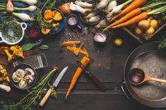 Mit Waldpilzen und Gemüsebestandteilen und Küchenwerkzeugen kochen, Vorbereitung auf dunklen rustikalen Holztisch Stockbild