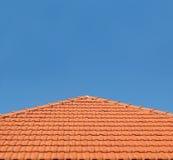 Mit Ziegeln gedeckte Dachspitze auf blauem Himmel Stockfoto