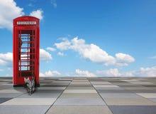 Mit Ziegeln gedeckter Hintergrund mit britischem Telefonkasten, Katze der getigerten Katze und blauem Himmel Stockfotos