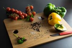Mitad amarilla verde de las pimientas del cuchillo y de los tomates del aguacate Imágenes de archivo libres de regalías
