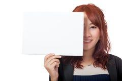 Mitad asiática del cierre de la sonrisa de la muchacha de oficina de su cara con la muestra en blanco Fotografía de archivo