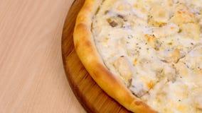 Mitad de cortar la pizza con los champi?ones y el queso de las setas en el tablero de madera en la tabla vista lateral del primer almacen de metraje de vídeo