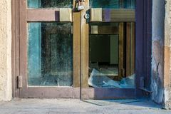 Mitad de la puerta de cristal vieja quebrada con la cerradura de acero foto de archivo