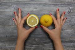 Mitad de un limón en la mano izquierda y limón entero en la mano derecha Fotos de archivo