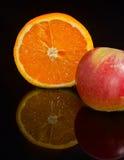 Mitad de una naranja y de una manzana Fotos de archivo libres de regalías