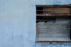 Mitad de una ventana de una casa azul acera imagenes de archivo
