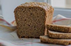 Mitad del pan negro hecho en casa con algunas rebanadas en la toalla de lino imagen de archivo