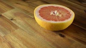 Mitad del pomelo rojo que gira en la tabla de madera metrajes