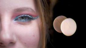 Mitad-retrato del primer de la muchacha rubia caucásica hermosa con maquillaje colorido brillante en fondo borroso de las luces almacen de video