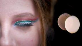 Mitad-retrato del primer de la muchacha rubia caucásica hermosa con maquillaje colorido extraordinario en luces borrosas metrajes
