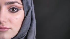 Mitad-retrato del primer de la mujer musulmán hermosa en hijab con maquillaje de moda que mira tranquilamente en cámara en negro almacen de video