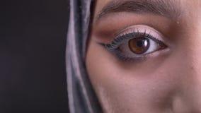 Mitad-retrato del primer de la mujer musulmán joven en hijab con maquillaje de moda que mira hacia abajo en fondo negro almacen de video