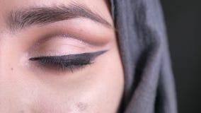 Mitad-retrato del primer de la mujer musulmán joven hermosa en hijab con maquillaje que mira en cámara en fondo negro almacen de video
