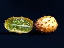 Mitad y frutas enteras del kiwano en el contexto negro imágenes de archivo libres de regalías