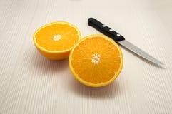 Mitades anaranjadas y un cuchillo Imagen de archivo