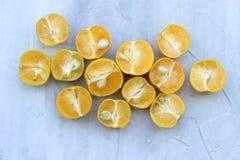 Mitades brillantes de la fruta c?trica y zumo de naranja en fondo gris La visi?n desde la tapa imagen de archivo libre de regalías