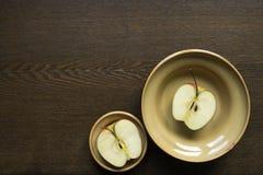 Mitades de Apple en platos de la arcilla en el tablero de madera Fotos de archivo libres de regalías
