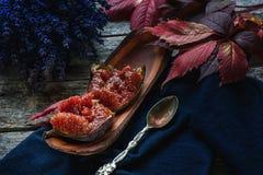 Mitades de higos maduros con una cuchara en un fondo de la lavanda y hojas de un otoño hermosas Primer rústico Fotos de archivo libres de regalías