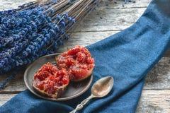 Mitades de higos maduros con una cuchara en un fondo de la lavanda y hojas de un otoño hermosas Primer rústico Imagen de archivo libre de regalías