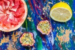 Mitades de la fruta de la pasión, del limón y del pomelo en un backgro colorido Fotografía de archivo