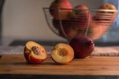 Mitades de la nectarina en la tajadera Imagen de archivo libre de regalías