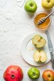 Mitades de manzanas en la miel en una placa de cerámica, granada en una tabla blanca Foto de archivo libre de regalías