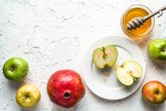 Mitades de manzanas en una placa, una granada y una miel en una tabla blanca Foto de archivo libre de regalías