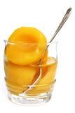 Mitades de melocotones en un jarabe dulce en un vidrio Imagen de archivo libre de regalías