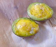 Mitades del aguacate cocidas con los huevos Foto de archivo