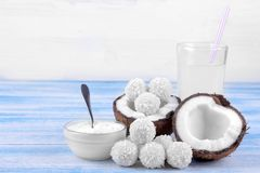 Mitades del coco con los dulces del coco, el aceite de coco fresco y la leche Foto de archivo libre de regalías
