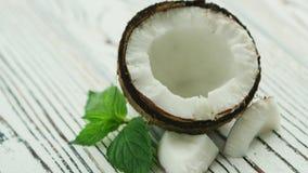 Mitades del coco fresco con las hojas de menta metrajes