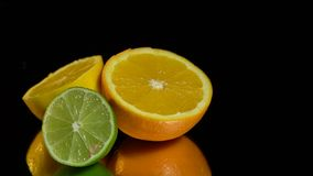 Mitades del limón, de la naranja y de la cal en un fondo negro almacen de metraje de vídeo