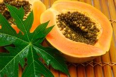 Mitades frescas de la papaya y hoja verde Imágenes de archivo libres de regalías