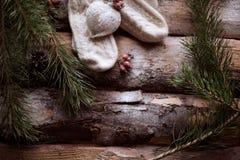 Mitaines blanches avec un jouet-coeur blanc sur les planches en bois avec les branches impeccables et les baies rouges tout autou Image stock