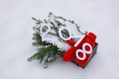 Mitaines rouges, nombres de papier et branches d'arbre vertes de sapin dans la boîte décorative en bois sur la neige Photo libre de droits