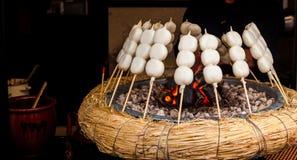 Mitarashi Dango auf Feuer lizenzfreie stockfotos
