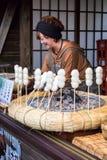 Mitarashi Dango. Oshino Japan - November 22 2017: Mitarashi Dango is a Japanese dumpling and sweet made from mochi with female trader, Dango famous of street Stock Photos