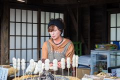 Mitarashi Dango. Oshino Japan - November 22 2017: Mitarashi Dango is a Japanese dumpling and sweet made from mochi with female trader, Dango famous of street Royalty Free Stock Image