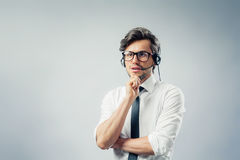 Employee thinks. Employee with headset thinks Royalty Free Stock Photos
