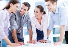 Mitarbeiter, die über Tabelle sich lehnen Lizenzfreie Stockbilder