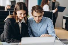 Mitarbeiter, die einen Computer betrachten und über Arbeit sprechen lizenzfreies stockfoto