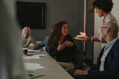 Mitarbeiter, die Geburtstag des weiblichen Kollegen mit Kuchen feiern Stockbilder